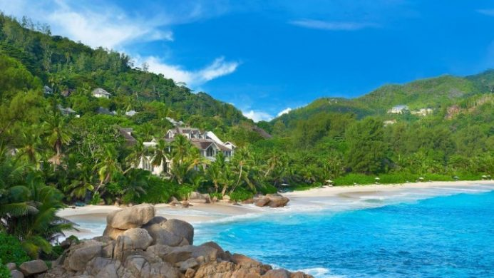 Banyan Tree Seychelles view of white sandy beach and turquoise water with hotel beyond
