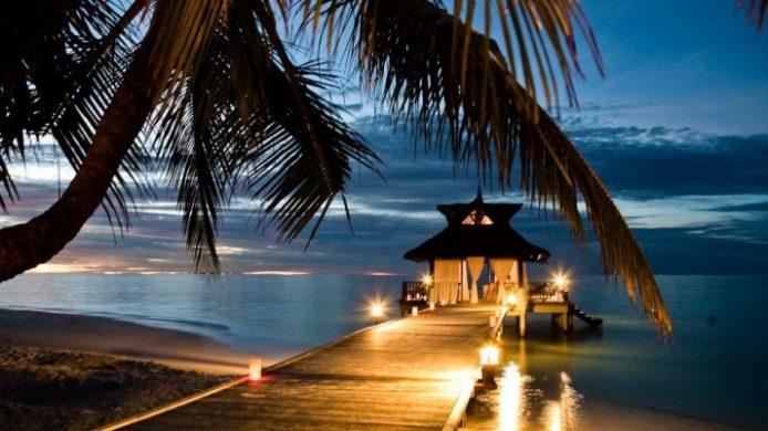 Banyan Tree Maldives Vabbinfaru dock and palm tree at sunset