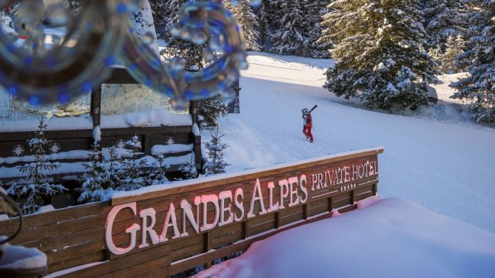 Grandes Alpes sign with skier behind