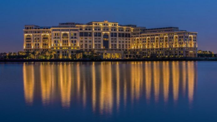 palatial hotel at nightfall with lights reflecting in water
