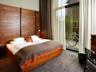 25hours Hotel HafenCity bedroom with wool blanket and patio with bicycle