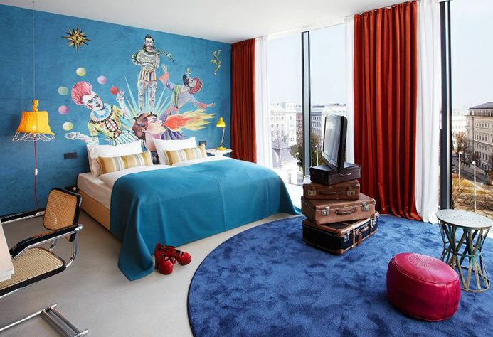 25hours Hotel Wien suite with clown mural and vintage luggage set