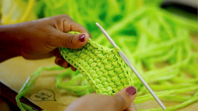 Close up of women's hands with crochet project