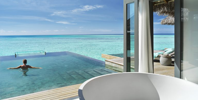 Vakkaru Maldives overwater villa with woman in private pool