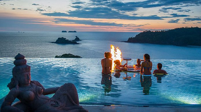 Casa Chameleon Hotel at Las Catalinas infinity pool with fire at sunset