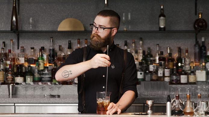Fairmont Pacific Rim's bartender mixing a cocktail