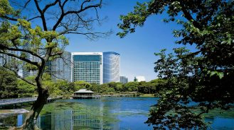 Exterior view of Conrad Tokyo with gardens and water