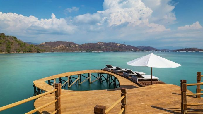 AYANA Komodo Resort's overwater jetty with loungers facing the sea