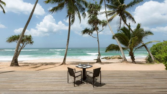 Amanwella Resort's open patio on beach with table and chairs