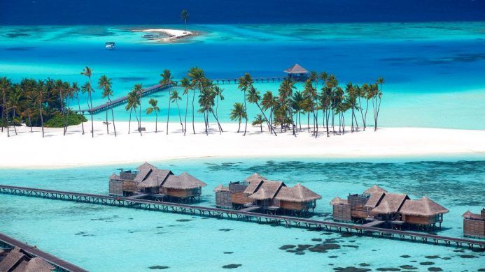 Gili Lankanfushi Resort's overwater villas with white sand beach in the background