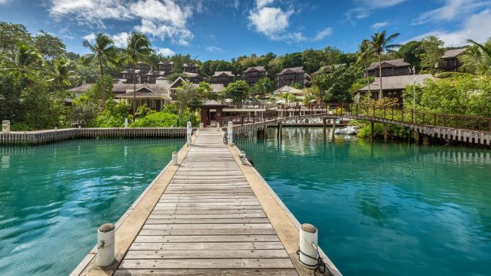 Overwater walkway leading to resort amidst palm tree forest