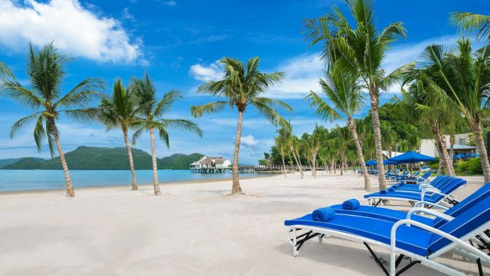 The St. Regis Langkawi blue loungers on beach with palm trees