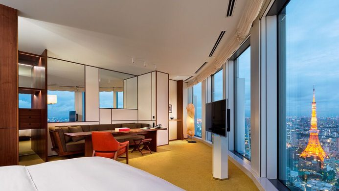 Room with curved windows overlooking evening cityscape and Tokyo Tower