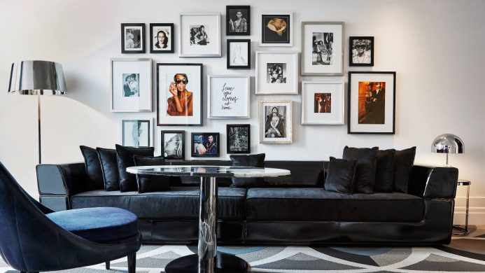 Blue couch with framed gallery wall at Bisha Hotel and Residences