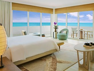 Corner bedroom with floor-to-ceiling views of the turquoise ocean