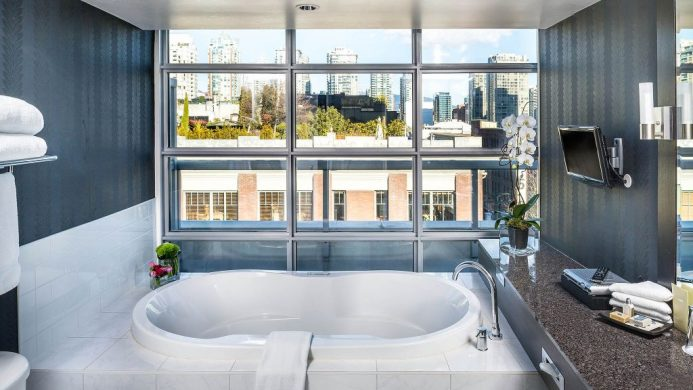 Suite bathroom with windows overlooking city at Opus Hotel Vancouver