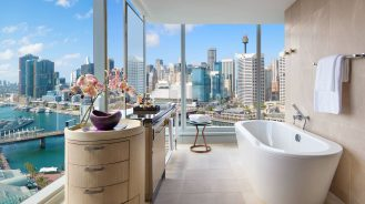 Corner bathroom with floor-to-ceiling views of the city at Sofitel Sydney Darling Harbour