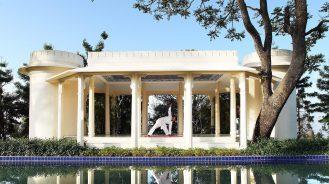 Man doing yoga in a white garden pavilion