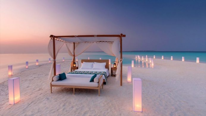 Four poster bed on isolated sandbank at dusk