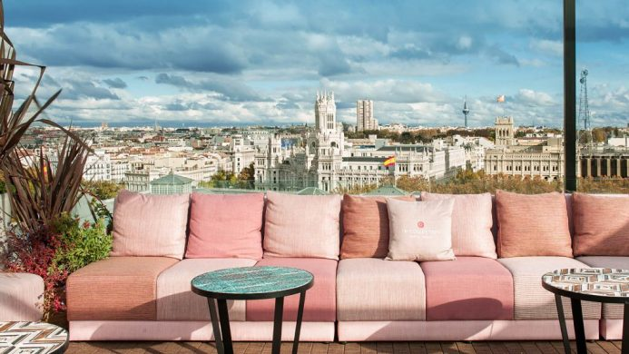 NH Collection Madrid Suecia: rooftop lounge with pink sofa and views of Madrid