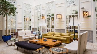 Only You Boutique Hotel - lobby lounge with white mirrored walls, indoor plants and natural light