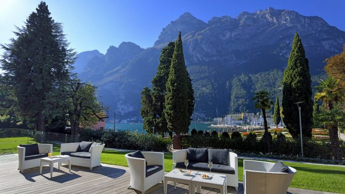Lido Palace's open patio seating overlooking lake and mountain peaks