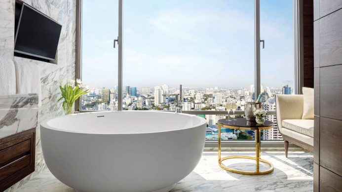 Round bathtub in marble bathroom with floor-to-ceiling window view of Bangkok