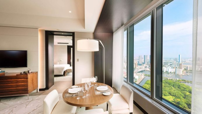 Suite with dining area and windows overlooking Tokyo and green gardens