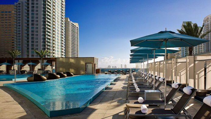 Rooftop pool with lounge chairs and umbrellas, surrounded by tall buildings