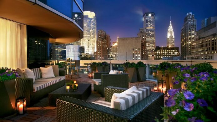 Large patio with lounge furniture and New York's lit up buildings in the background
