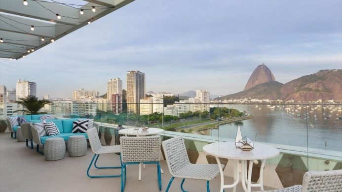 Roof patio with bistro chairs and tables, with an open-air view of the city, bay and mountains