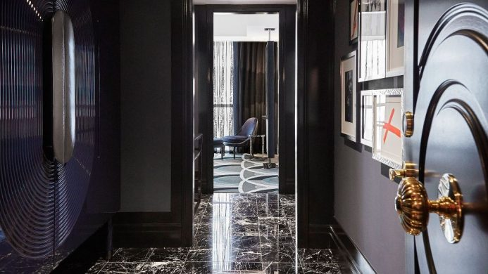 Bisha Hotel room entrance with gold doorknob, black marble tiles and gallery wall
