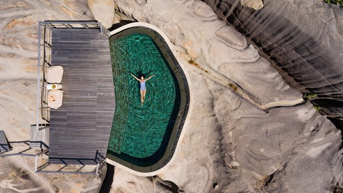 Aerial of woman floating pool over rocks at the SIx Senses Zil Pasyon