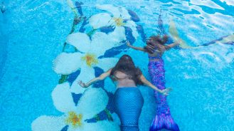 Adult and child swimming with mermaid tails at the Fairmont Kea Lani Maui