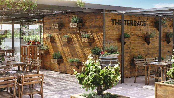 Terrace under a ivy covered wooden pergola at Fairmont Rey Juan Carlos