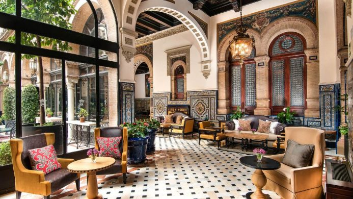 Hotel Alfonso XIII glass-enclosed sitting area with Arabic architecture, looking out to garden