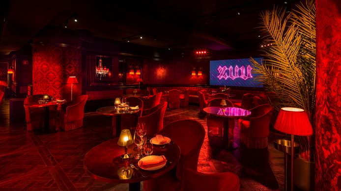 Dark restaurant and stage with red velvets at Hotel SOFIA Barcelona's Zuu restaurant and cabaret