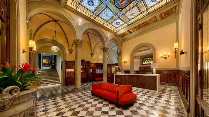 NH Collection Firenze hotel reception with arched columns and stained glass ceiling