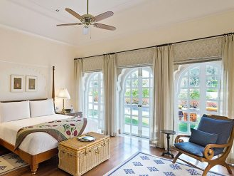 The Oberoi Sukhvilas suite bedroom with glass doors to gardens