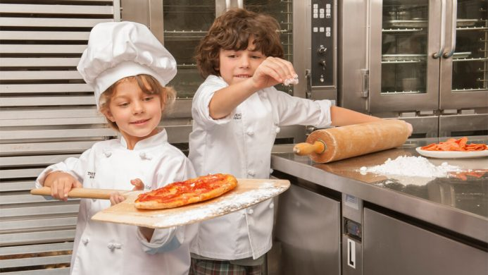 Kids making pizza in chefs whites at The Peninsula Beverly Hills