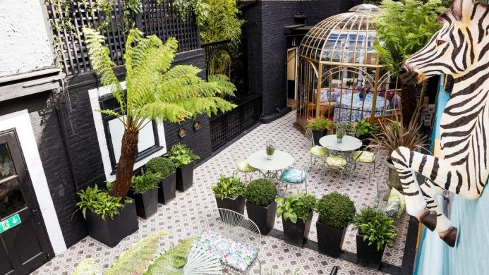 Blakes Hotel London courtyard garden with mosaic tiles, birdcage seating and zebra wall sculpture