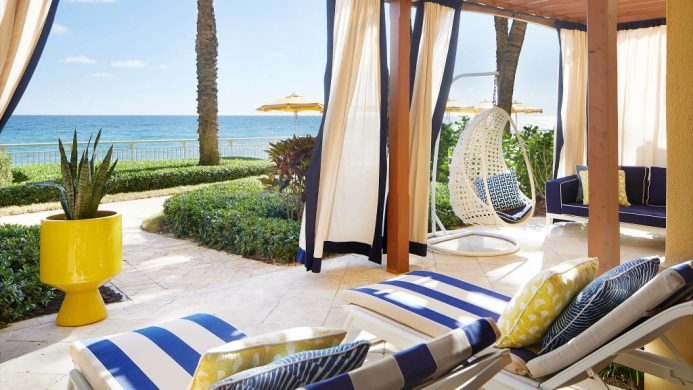 Oceanfront lanai with nautical curtains and loungers and a swing chair at the Eau Palm Beach Resort and Spa