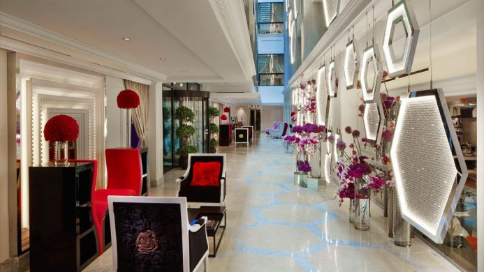 Fashionable chairs and geometric walls with red details at the SO Sofitel Singapore lobby