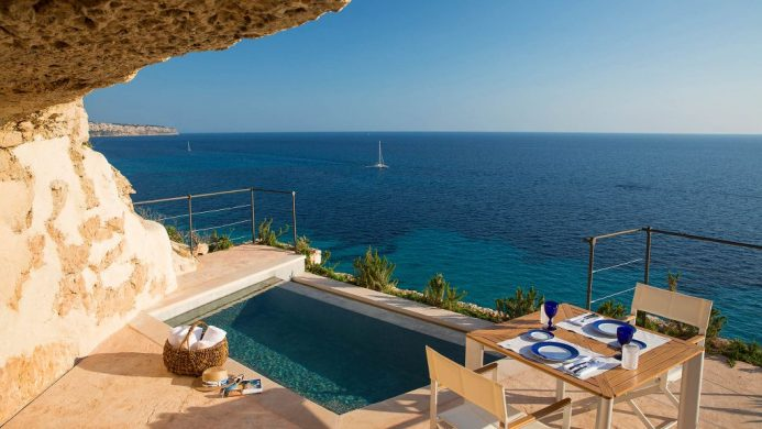 Plunge pool overlooking blue waters and sailboat under within sandstone