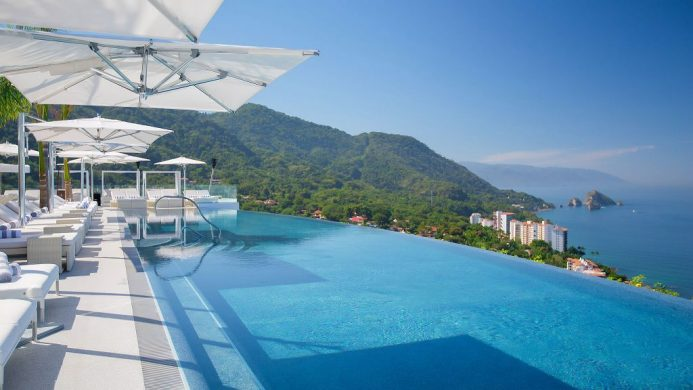 Hotel Mousai rooftop infinity pool towering over forested mountains and the ocean