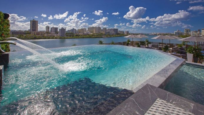 Rooftop pool with waterfall fountain overlooking lagoon and tall buildings beyond