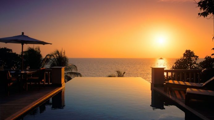 Trisara villa infinity pool looking out to an orange sunset