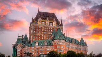 Exterior of Fairmont Le Chateau Frontenac in front of a fiery sky