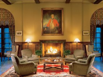 Lounge with fireplace and oil painting at Fairmont Le Manoir Richelieu