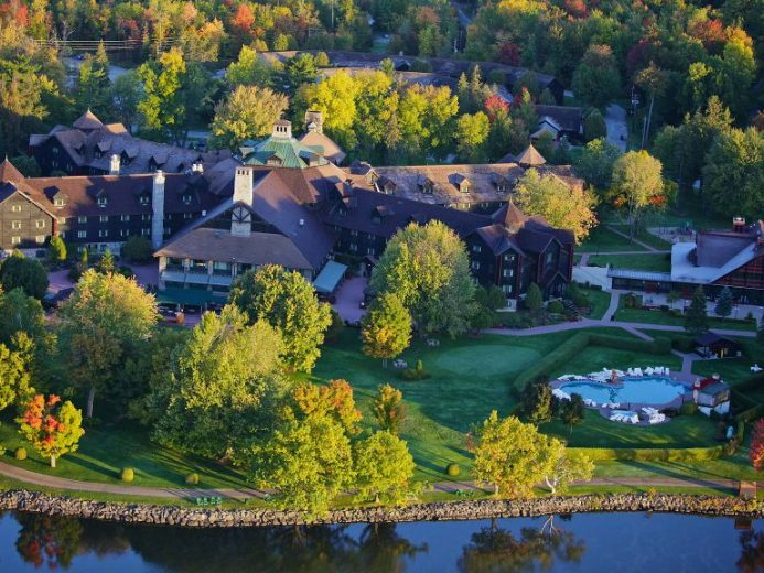 Aerial view of Fairmont Le Chateau Montebello amidst lush forests and a river
